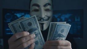 Cherkassy, Ucrania, el 4 de enero de 2019: anónimo en la máscara de Guy Fawkes cuenta de nuevo cuentas de los dólares ganados par almacen de video