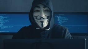 Cherkassy, Ucrania, el 10 de enero de 2019: Pirata informático anónimo en la sudadera con capucha negra que oculta su cara bajo m metrajes