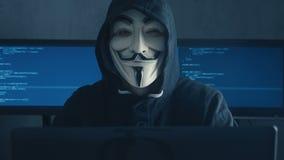 Cherkassy, Ucrania, el 10 de enero de 2019: Pirata informático anónimo en la sudadera con capucha negra que oculta su cara bajo m almacen de video