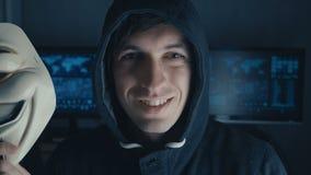 Cherkassy, Ucrania, el 10 de enero de 2019: Pirata informático anónimo en la sudadera con capucha negra que oculta su cara bajo m almacen de metraje de vídeo