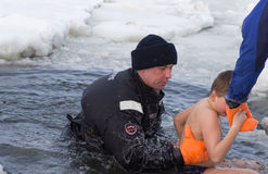 Cherkassy, Ukraine - January 19, 2016: lifeguard rescues a boy pulling it from the ice-cold water Stock Image