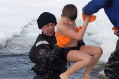 Cherkassy, Ukraine - January 19, 2016: lifeguard rescues a boy pulling it from the ice-cold water Stock Images