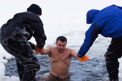 Cherkassy, Ukraine - January 19, 2016: lifeguard rescues a boy pulling it from the ice-cold water Stock Photos