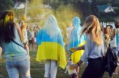 Cherkasy, Ucrânia, o 24 de agosto de 2018 - a festa do Holi no parque, pessoa em capas de chuva azuis e amarelas foto de stock