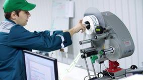 CHERKASY, UCRÂNIA - 24 DE AGOSTO DE 2018: o rolo do papel das mudanças do trabalhador com etiquetas da marcação em uma máquina co filme
