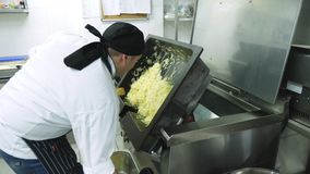 CHERKASY, UCRANIA, EL 20 DE FEBRERO DE 2019: un cocinero presenta, vierte mucha cebolla frita de un sartén industrial grande metrajes
