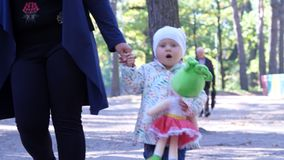 Cherkasy, Ukraina, Październik 17, 2018: mała, ładna dwuletnia dziewczyna, chodzi, trzymający mamy rękę w jesień parku, zbiory