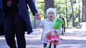 Cherkasy, Ukraine, am 17. Oktober 2018: kleine, recht zweijährige Mädchenwege, die Hand der Mutter, im Herbstpark halten stock footage