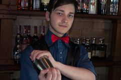 Handsome bartender making  drink with sheker in bar royalty free stock image
