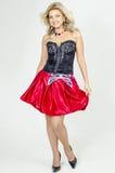 chermnm束腰的美丽的白肤金发的妇女艺术家有衣服饰物之小金属片的和有传送带的红色裙子鞠躬 图库摄影