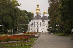 Chernigov, Ukraine 15. September 2017 Christliche orthodoxe weiße Kirche mit grauen Hauben und Goldkreuzen Park mit Blumen ruhe Lizenzfreie Stockbilder