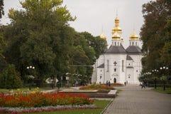 Chernigov, Ukraine 15. September 2017 Christliche orthodoxe weiße Kirche mit grauen Hauben und Goldkreuzen Park mit Blumen ruhe Lizenzfreie Stockfotografie