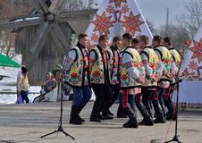 Folklore men collective perfoms national dancing during the ethnic festival of Christmas Carols in open-air museum,Ukraine royalty free stock image