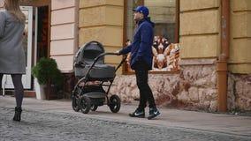 14 11 2017 Chernivtsi, de Oekraïne - de jonge mooie vader met wandelwagen loopt op de straat stock footage
