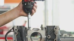 19 07 Chernivtsi 2018 - el trabajador está desmontando el motor de coche en un taller de reparaciones, torciendo los pernos almacen de video