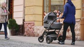 14 11 2017 Chernivtsi, Ucrania - el padre hermoso joven con el cochecito está caminando en la calle almacen de metraje de vídeo