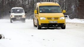 23 03 2018 Chernivtsi, Ucrania - los coches montan por el camino entre árboles helados en bosque en el día de invierno Imagen de archivo libre de regalías