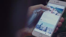 Chernivtsi/Ucrania - 02 25 2018: Tenencia de la mano del primer y smartphone femeninos con usando instagram, en la noche con el b almacen de metraje de vídeo
