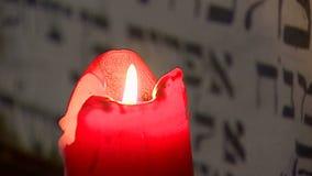 Chernivtsi. Ukraine. 07/27/2019. Burning candle on the background of the Jewish Torah.
