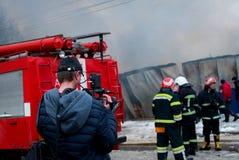 Chernivtsi/Ukraine - 03/19/2018: Löschfahrzeug mit Sirenen und Blaulichtern mit Feuer auf Hintergrund Korrespondent mit Kamera ve Lizenzfreies Stockbild