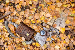 Chernobyl, the consequences of the terrible tragedy. Decompose protective mask lying in fallen leaves on the ground beside to the decaying opened chemistry Royalty Free Stock Photo