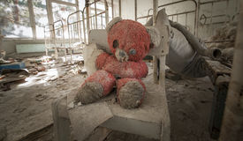 Chernobyl - Teddy bear in abandoned kindergarten. Old red teddy bear sitting on a chair in an abandoned kindergarten in Pripyat - Chernobyl nuclear power plant royalty free stock photos