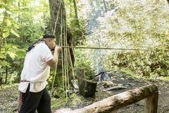 Cherokee facendo uso della pistola ad aria compressa tradizionale Fotografie Stock Libere da Diritti
