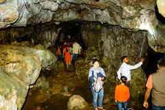 Cherrapunjee, Meghalaya, May 6: Group of tourists visiting Mawsmai Cave. Narrow, rugged limestone cave with dimly-lit access point stock photos