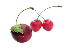 Cherries. Three cherries - one with a leaf and two in the background Stock Photo