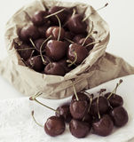Cherries. Paper bag full of cherries.  Vintage color treatment Royalty Free Stock Photography