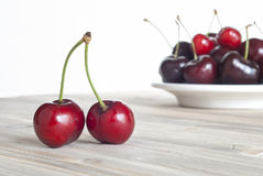 Cherries on aged wood on the plate. Aged wood and white background Royalty Free Stock Photo