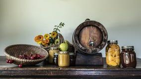 Cherries apples flowers jam jars and a barrel Stock Image
