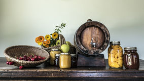 Cherries apples flowers jam jars and a barrel Royalty Free Stock Photography