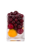 Cherries, apricots and plums in glass on white background Royalty Free Stock Photo