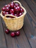 Cherries in the basket on the dark textured wooden planks Stock Photos