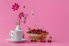 Cherries in the basket on a pink background with leaves and flow Stock Image