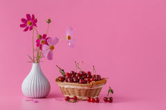 Cherries in the basket on a pink background with leaves and flow Royalty Free Stock Photos