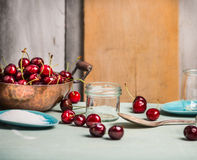 Cherries berries preserving with glass jar on rustic kitchen table Royalty Free Stock Images