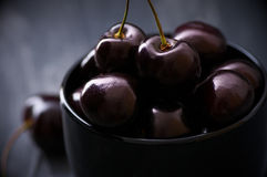 Cherries in black bowl Royalty Free Stock Photos