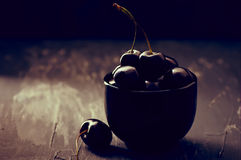 Cherries in black bowl Stock Images