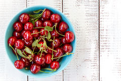 Cherries in a blue bowl on a white wooden background Stock Images