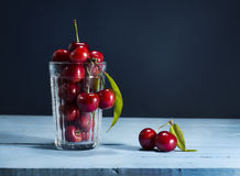 Cherries on a blue wooden background. Cherries in glass on a blue wooden background royalty free stock photo