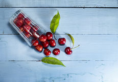 Cherries on a blue wooden background. Top view. Cherries in glass on a blue wooden background.Top view stock photography