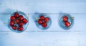 Cherries on a blue wooden background. Top view. Cherries in glass saucers on a blue wooden background.Top view stock photo
