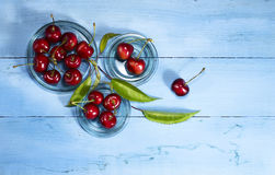 Cherries on a blue wooden background. Top view. Cherries in glass saucers on a blue wooden background.Top view stock photography