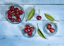 Cherries on a blue wooden background. Top view. Cherries in glass saucers on a blue wooden background.Top view royalty free stock photography