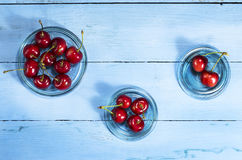 Cherries on a blue wooden background. Top view. Cherries in glass saucers on a blue wooden background.Top view royalty free stock photos