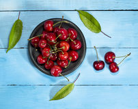 Cherries on a blue wooden background. Top view. Cherries in saucers on a blue wooden background.Top view royalty free stock image