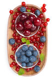 Cherries, blueberries and red currants in a wooden bowl isolated Royalty Free Stock Image