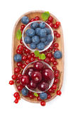 Cherries, blueberries and red currants in a wooden bowl isolated Royalty Free Stock Images